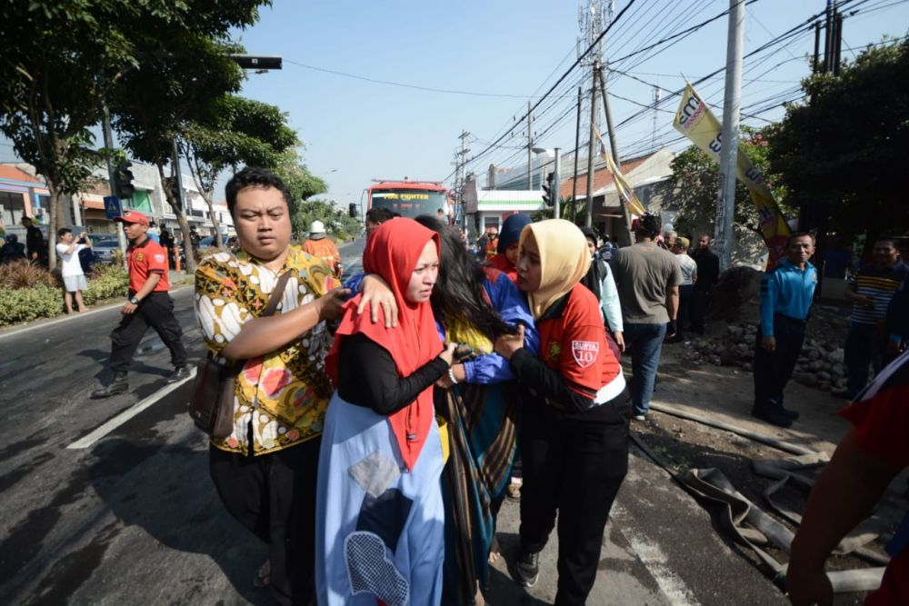 Patugas membopong salah satu penghuni Asrama Polisi Tandes yang terbakar