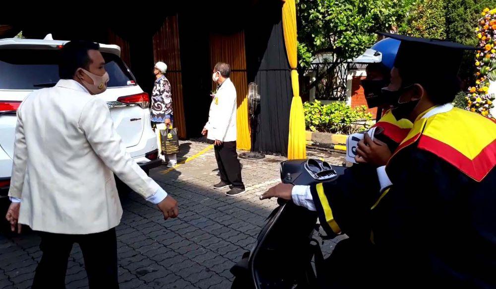 Para wisudawan menunggu giliran di atas kendaraannya masing-masing dalam wisuda drive thru UWK Surabaya
