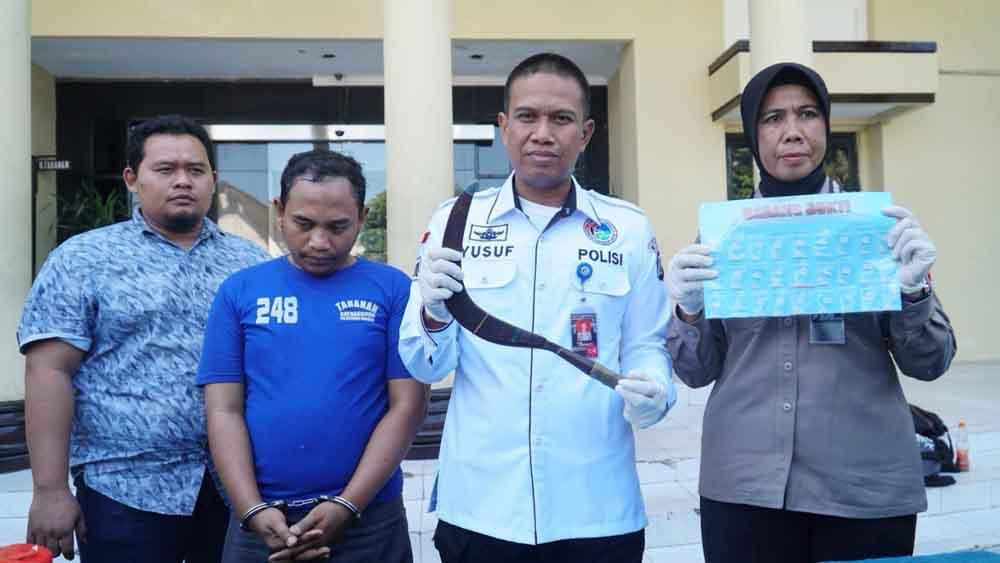 Tersangka (baju biru) saat berada di Mapolrestabes Surabaya