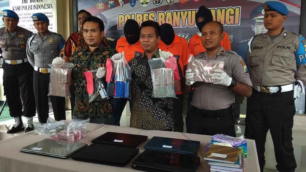 Kasat Reskrim Polres Banyuwangi, AKP Panji Pratistha Wijaya menunjukkan barang bukti berupa uang tunai ratusan juta