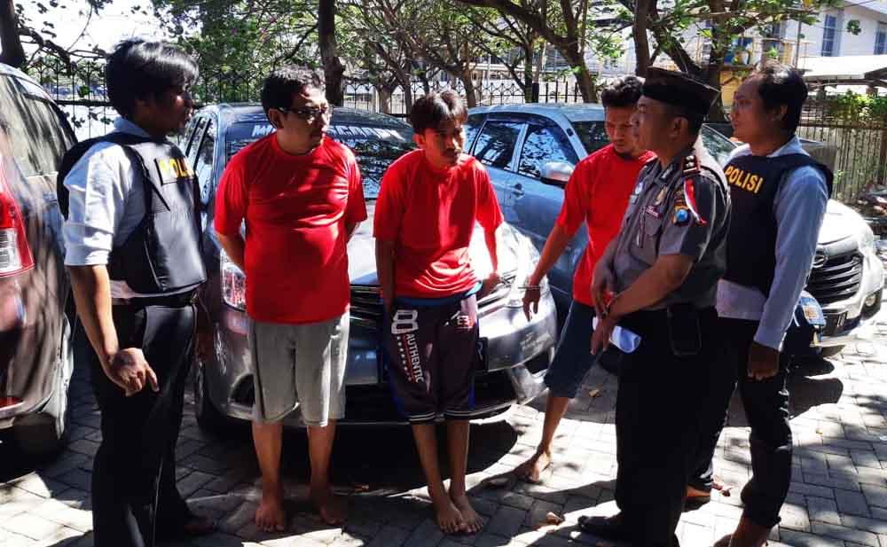 Tiga tersangka bersama barang bukti mobil rental saat berada di Mapolsek Tenggilis Surabaya