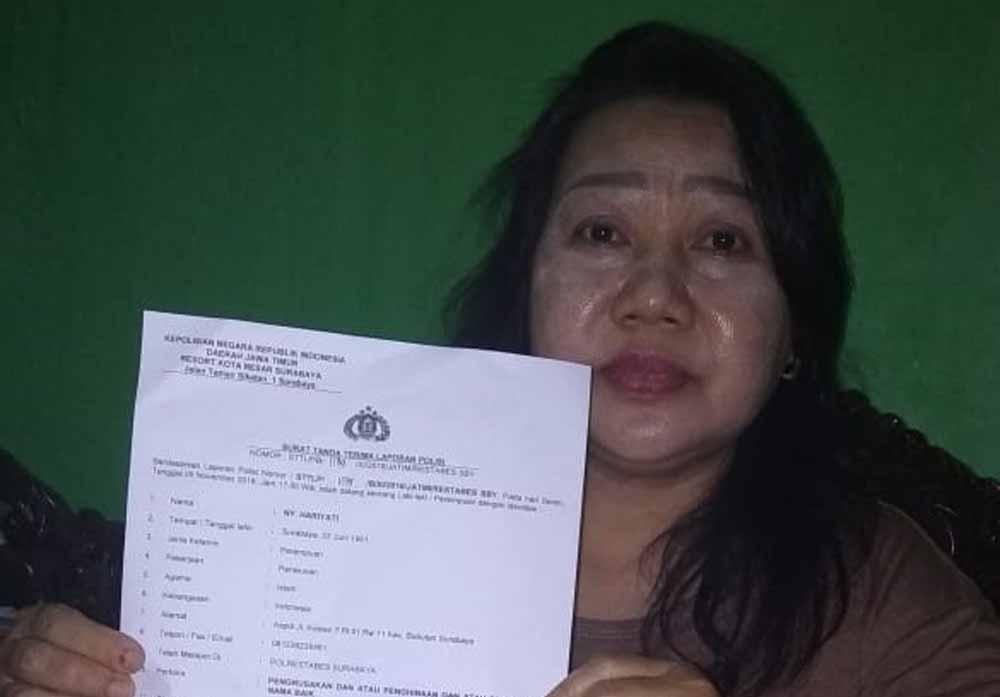 Hariyari menunjukkan Surat Tanda Laporan Polisi yang ia buat di Polrestabes Surabaya