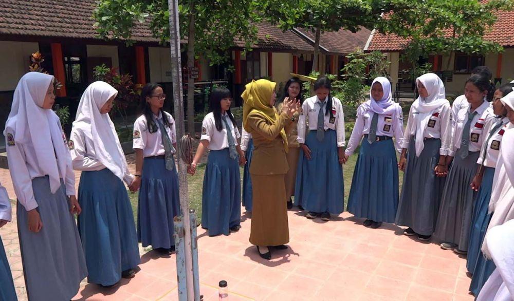 Para siswa berdiri di lapangan untuk merasakan dan memperlajari hari tanpa bayangan di Tulungagung